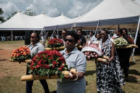 Les participants portent des fleurs pendant les funérailles de masse pour enterrer 81 cercueils contenant les restes récemment découverts de 84437 victimes du génocide rwandais de 1994
