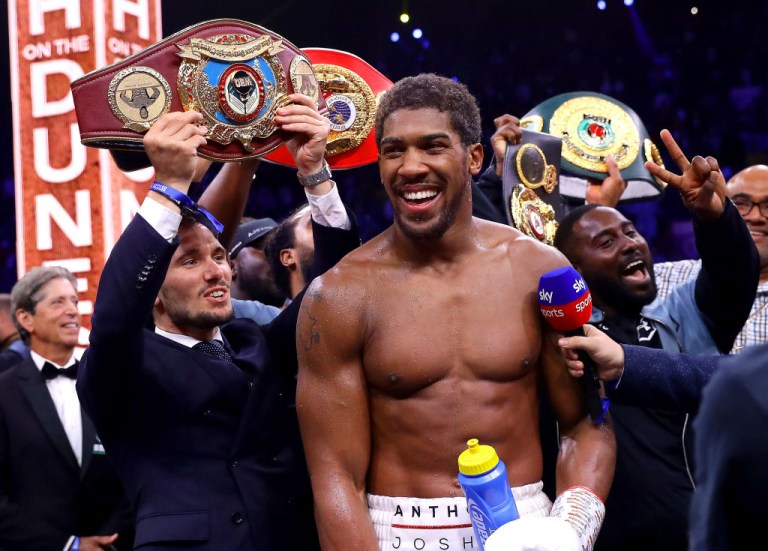 Anthony Joshua smiles surrounded by his heavyweight titles