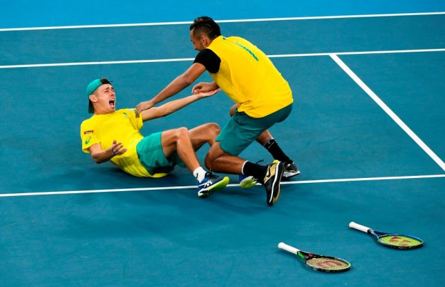 Nick Kyrgios collapses to the ground with Alex de Minaur after Australia beat Great Britain in the ATP Cup