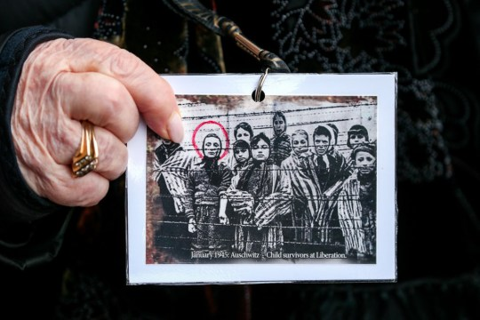 A hand holds a black and white photo of prisoners in Auschwitz