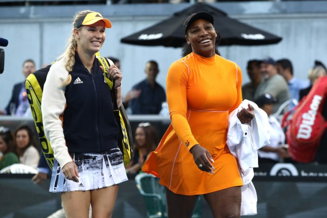 Caroline Wozniacki and Serena Williams smile as they walk on court at the ASB Classic in Auckland