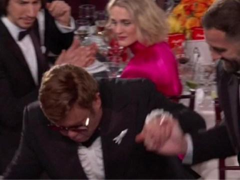 Elton John nearly takes a tumble on his way to collect Golden Globe