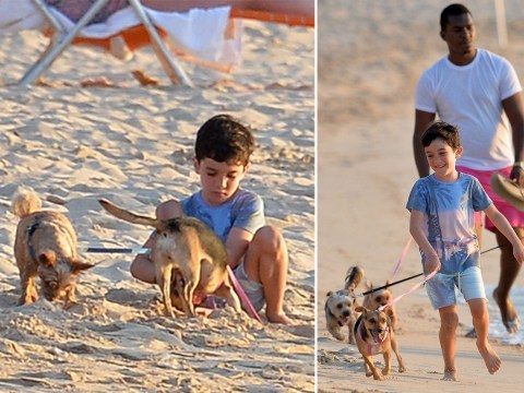 Simon Cowell's son Eric takes his dogs for a walk on the beach as they give us further holiday envy