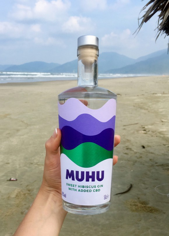 The Muhu gin held in Sally Wynter's hand while on the beach