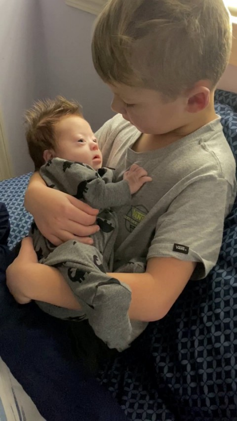 Six year old sings Bieber song to newborn Downs baby brother (Picture: SWNS)