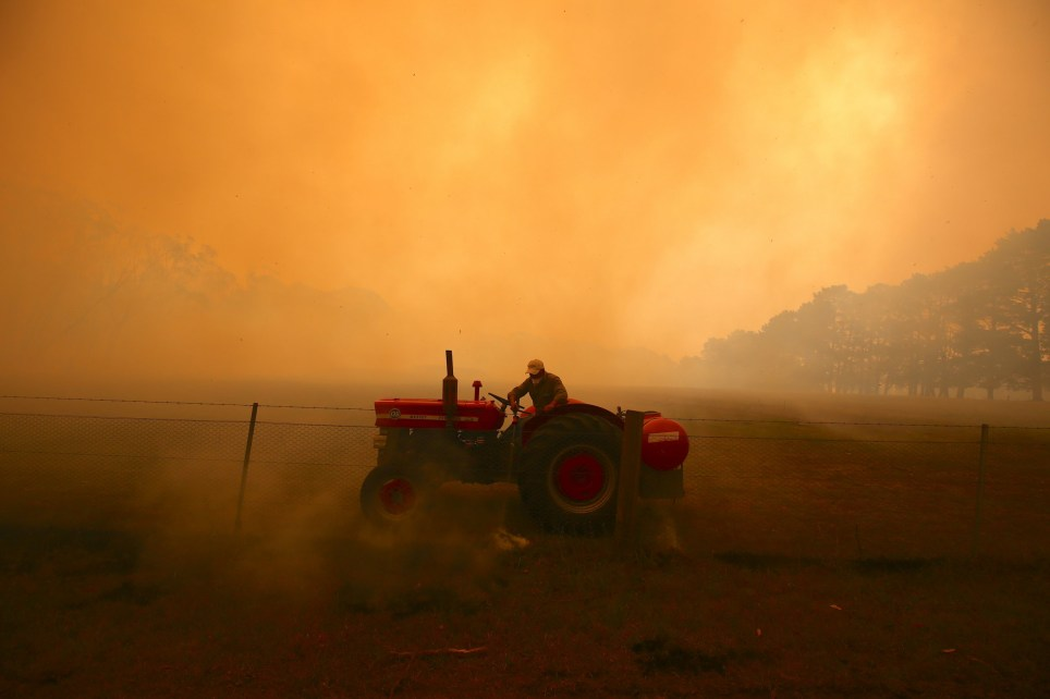 SYDNEY, AUSTRALIA - DECEMBER 19: A farmer drives a tractor as he uses a hose to put out a fire burning in his paddock and near homes on the outskirts of the town of Bilpin on December 19, 2019 in Sydney, Australia. (Photo by David Gray/Getty Images) *** BESTPIX ***