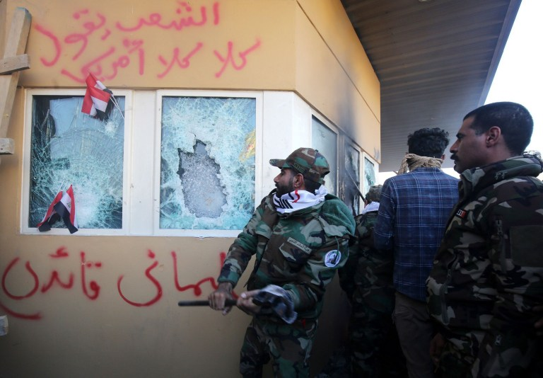 """Members the Hashed al-Shaabi, a mostly Shiite network of local armed groups trained and armed by powerful neighbour Iran, smash the bullet-proof glass of the US embassy's windows in Baghdad after breaching the outer wall of the diplomatic mission on December 31, 2019 to vent their anger over weekend air strikes that killed pro-Iran fighters in western Iraq. - It was the first time in years protesters have been able to reach the US embassy in the Iraqi capital, which is sheltered behind a series of checkpoints in the high-security Green Zone. Arabic writing on the wall reads: """"The people say no, no, to America"""" (top) and the commander of the Iranian Revolutionary Guard's Quds Force, General Qassem """"Suleimani is my leader"""". (Photo by AHMAD AL-RUBAYE / AFP) (Photo by AHMAD AL-RUBAYE/AFP via Getty Images)"""