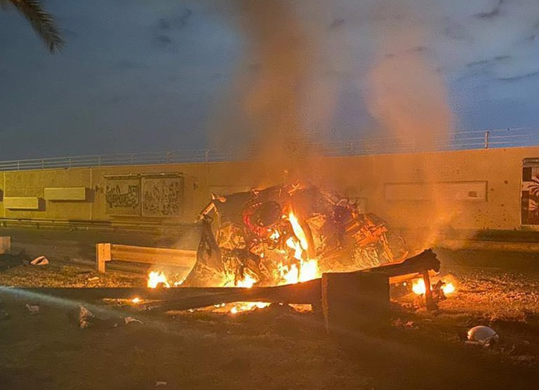 """A picture published by the media office of the Iraqi military's joint operations forces on their official Facebook page shows a destroyed vehicle on fire following a US strike on January 3, 2020 on Baghdad international airport road in which top Iranian commander Qasem Soleimani was killed along with eight others, including the deputy head of Iraq's powerful Hashed al-Shaabi paramilitary force. - Early Friday, a volley of US missiles hit Baghdad's international airport, striking a convoy belonging to the Hashed al-Shaabi, an Iraqi paramilitary force with close ties to Iran. Soleimani was killed in the US strike on the Iraqi capital's airport, according to Hashed, in a dramatic escalation of tensions between Washington and Tehran. (Photo by - / IRAQI MILITARY / AFP) / === RESTRICTED TO EDITORIAL USE - MANDATORY CREDIT """"AFP PHOTO / HO / IRAQI MILITARY"""" - NO MARKETING NO ADVERTISING CAMPAIGNS - DISTRIBUTED AS A SERVICE TO CLIENTS === (Photo by -/IRAQI MILITARY/AFP via Getty Images)"""