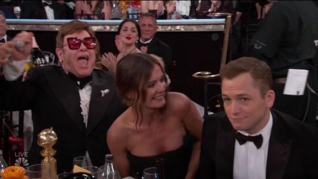 """BGUK_1829446 - Los Angeles, CA - Elton John appears ecstatic as Taron Egerton wins Golden Globe for playing him in Rocketman. The British singing superstar screamed with joy as Egerton was named Best Actor in a Motion Picture, Musical or Comedy. Egerton then went on to thank Sir Elton for: """"Being My Friend,"""" in his touching Golden Globes acceptance speech. Egerton beat out fellow nominees Daniel Craig, (Knives Out), Leonardo DiCaprio (Once Upon a Time??? in Hollywood), Roman Griffin Davis (Jojo Rabbit), and Eddie Murphy (Dolemite Is My Name) for his first ever Globes win. While accepting the award, Egerton thanked Elton for inspiring the film and working closely by his side. ???Thank you for the music, thank you for living a life less ordinary and thank you for being my friend,??? Egerton said. The actor added that being a part of Rocketman 'changed my life'. ???It has been the best experience of my life. I???m so proud of the film,??? he continued. ???Everyone standing up for Elton and Bernie earlier, it???s just such a joyous thing. And we???ve loved every second.??? Along with Egerton???s win, Rocketman scored a nomination for Best Motion Picture, Drama and took home the award for Best Original Song in a Motion Picture. *BACKGRID DOES NOT CLAIM ANY COPYRIGHT OR LICENSE IN THE ATTACHED MATERIAL. ANY DOWNLOADING FEES CHARGED BY BACKGRID ARE FOR BACKGRID'S SERVICES ONLY, AND DO NOT, NOR ARE THEY INTENDED TO, CONVEY TO THE USER ANY COPYRIGHT OR LICENSE IN THE MATERIAL. BY PUBLISHING THIS MATERIAL , THE USER EXPRESSLY AGREES TO INDEMNIFY AND TO HOLD BACKGRID HARMLESS FROM ANY CLAIMS, DEMANDS, OR CAUSES OF ACTION ARISING OUT OF OR CONNECTED IN ANY WAY WITH USER'S PUBLICATION OF THE MATERIAL* Pictured: Taron Egerton, Elton John, Emily Thomas BACKGRID UK 5 JANUARY 2020 BYLINE MUST READ: NBC / BACKGRID UK: +44 208 344 2007 / uksales@backgrid.com USA: +1 310 798 9111 / usasales@backgrid.com *UK Clients - Pictures Containing Children Please Pixelate Face Prior To Publicatio"""