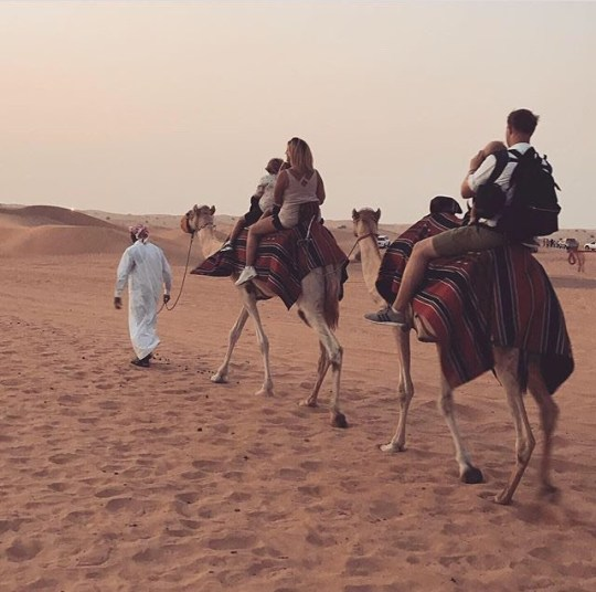 Farr family riding camels in Dubai. See SWNS story SWSYmaternity; Samantha Farr, 31, and husband Jonathan, 37, decided they were going to embark on their adventure when pregnant with George, now one. The teachers started planning just two weeks after he arrived in January 2019 and saved up, before splitting Samantha's maternity leave. Alongside older kids Archie, seven, and Teddy, three, they embarked on a three-month backpacking trip across eight countries and through twelve cities. They walked parts of the Great Wall of China and paddled over the Great Barrier Reef, surfed the Gold Coast and roamed the deserts of Dubai. They abandoned hopes of any sort of newborn routine, dealing with the sleepless nights in 19 different places, from hotels and tents to camper vans and hotels, rather than their home in Louth, Lincolnshire. Now back in the UK, the adventurous family are already missing the freedom and would urge others to follow in their footsteps next year.