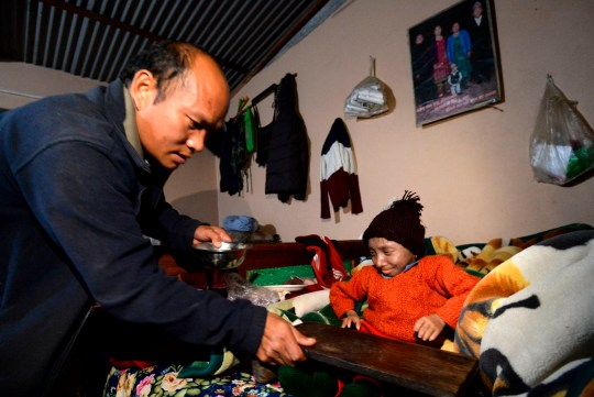 In this photograph taken on December 7, 2018, Khagendra Thapa Magar, the world's shortest man, is assisted by his father Rup Bahadur Thapa Magar before eating a meal at their home in Pokhara, some 200 kms west of Kathmandu. - The world's shortest man who could walk, as verified by Guinness World Records, died on Janaury 17, 2020 at a hospital in Nepal, his family said. Khagendra Thapa Magar, who measured 67.08 centimetres (2 feet 2.41 inches), died of pneumonia at a hospital in Pokhara, 200 kilometres from Kathmandu, where he lived with his parents. (Photo by PRAKASH MATHEMA / AFP) (Photo by PRAKASH MATHEMA/AFP via Getty Images)