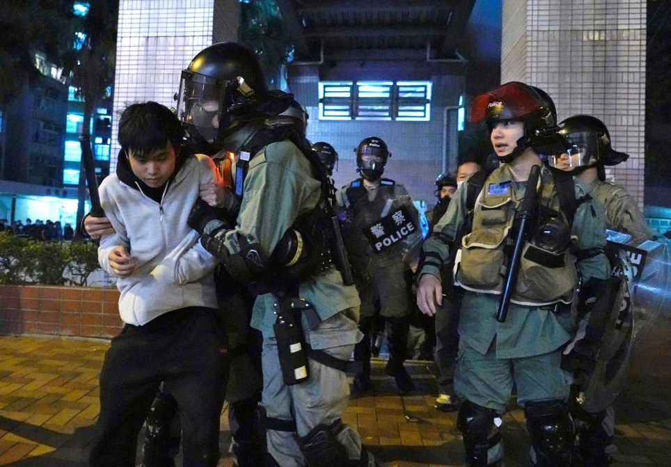 A local resident struggles with riot police at the Fai Ming Estate, in Fanling district of Hong Kong, Sunday, Jan. 26, 2020, after the Hong Kong government announced it would requisition an unoccupied housing project to house quarantined patients of the new viral coronavirus illness. Residents took the streets on Sunday night to oppose the plan to house quarantined patients or medical workers in their neighbourhood, that is far from Hong Kong's busy business centres. (AP Photo/Vincent Yu)
