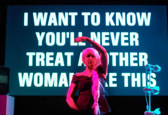 Louise Orwin on stage during her show Oh Yes Oh No with a screen depicting the words 'I want to know you'll never treat another woman like this' in the background