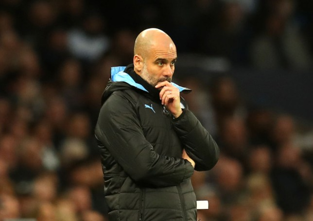 A worried Pep Guardiola looks on during a Manchester City