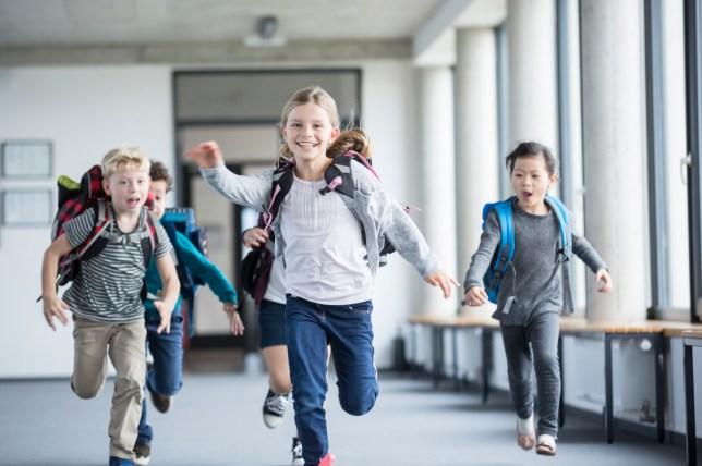Excited pupils rushing down school corridor.