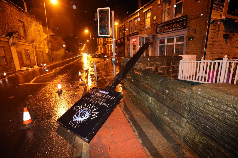A restaurant sign lays blown over in Luddendenfoot, West Yorkshire, where water levels have receded after the flooding of Storm Ciara.