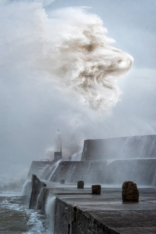 Moment waves smash over a lighthouse and form the perfect shape of a howling wolf, Porthcawl, South Wales. February 10, 2020.
