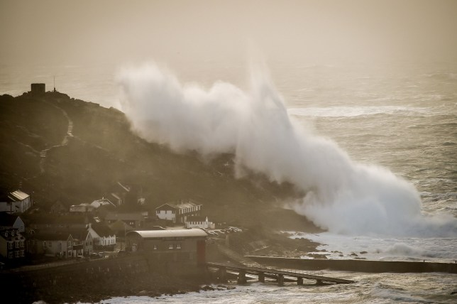 Waves crash on rocks and houses during Storm Ciara