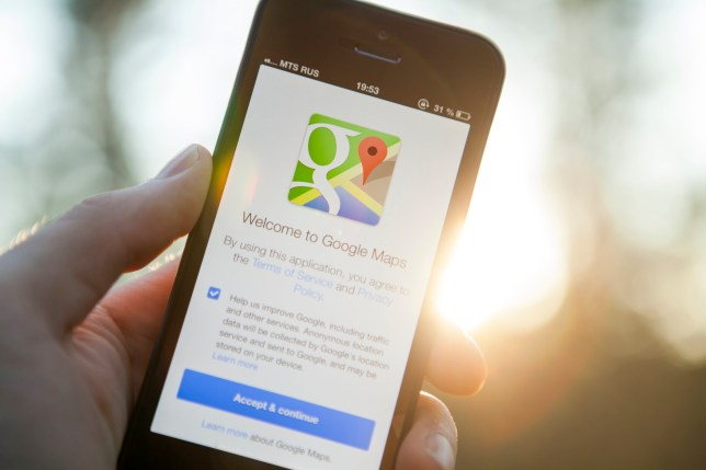 Moscow, Russia - August 29, 2013: Man hand holding iPhone 5 with Google Maps app on a sunset background. iPhone is product Apple Inc. Google Maps is a web mapping service application and technology provided by Google.