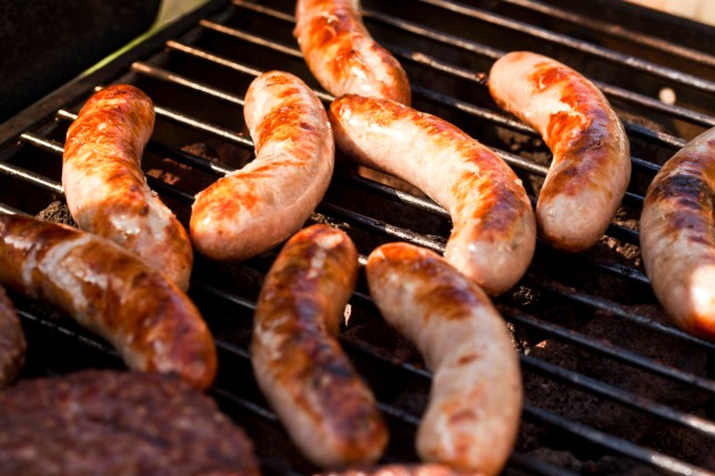 Cooking sausages and burgers on barbecue.