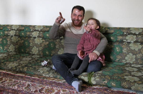 Syrian father Abdullah al-Mohammed sits with his three-year-old daughter Salwa at their home in Sarmada, a town in Syria's last rebel pocket in the Idlib province, which Russian-backed Syrian regime forces are trying to crush on February 19, 2020. - In Syria's Idlib, there's no escaping the war, so Abdullah al-Mohammed says the only way he found to reassure his daughter Salwa was to turn the shelling into a game. A video in which she laughs every time an explosion goes off was widely shared on social media in recent days as a heartening but grim reminder of Idlib residents' daily lives (Photo by Abdulaziz KETAZ / AFP) (Photo by ABDULAZIZ KETAZ/AFP via Getty Images)