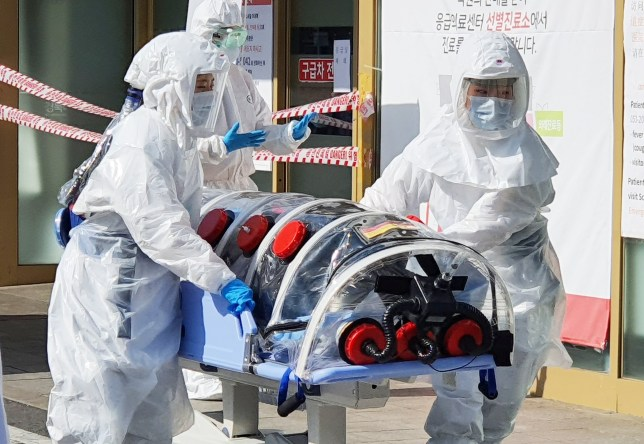 epa08227800 A patient suspected of carrying the new coronavirus, named COVID-19, arrives at Kyungpook National University Hospital in Daegu, South Korea, 19 February 2020. The city fell into chaos as 13 people residing there were found to have come down with the China-originated virus earlier in the day. EPA/YONHAP SOUTH KOREA OUT