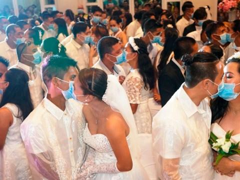 Newlyweds kiss through coronavirus masks in mass wedding in Philippines