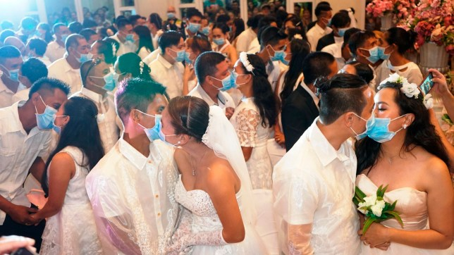 In this photo taken Feb. 20, 2020 and issued by the Bacolod City Public Information Office, Filipino couples kiss each other while wearing masks provided by the City Health Office in Bacolod city, Philippines. As part of efforts to prevent the spread of the new virus from China, 220 couples were required to fill in health declaration forms with their health status, and provide their travel history to the City Health Office before they were allowed to participate in a mass wedding solemnized by the Bacolod City mayor. (Bacolod City Public Information Office via AP)