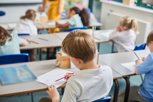 A boy sitting at a school desk