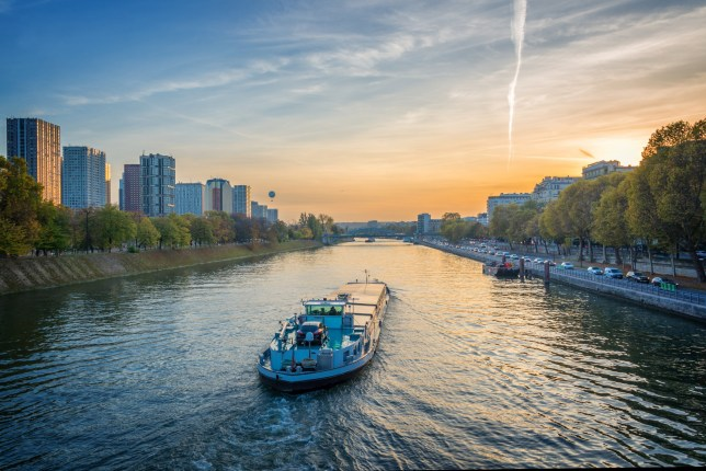 A stock image of a barge on the river Seine at sunset, Paris France