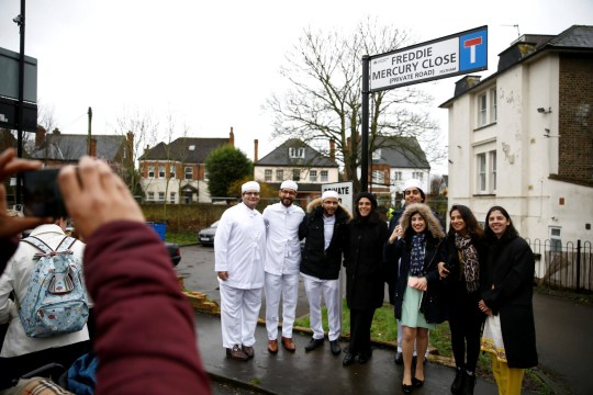 "People pose for a picture under the unveiled sign to rename a street in Feltham ""Freddie Mercury Close"", in Greater London, Britain February 24, 2020. REUTERS/Henry Nicholls"