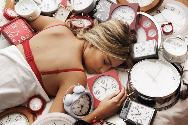 Woman sleeping on top of lots of clocks
