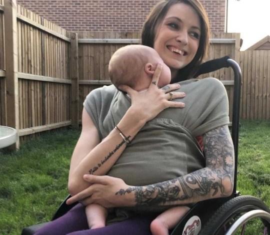 Emma Matthews sat in her wheelchair, holding her baby