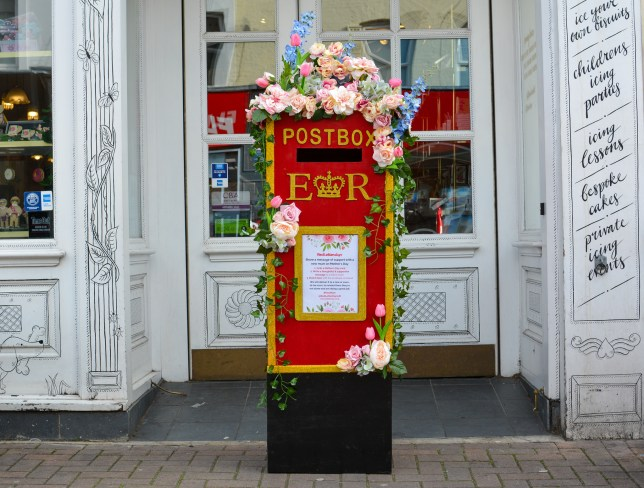 The first post box at Biscuiteers in London. The shop is behind it and it has pastel flowers on top and vines down the side.