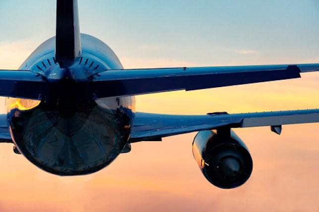 plane flying against sunset
