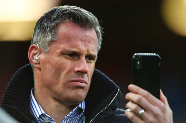 Jamie Carragher reads a text on his phone