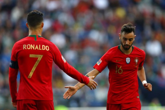 Cristiano Ronaldo from Portugal talks to Bruno Fernandes from Portugal