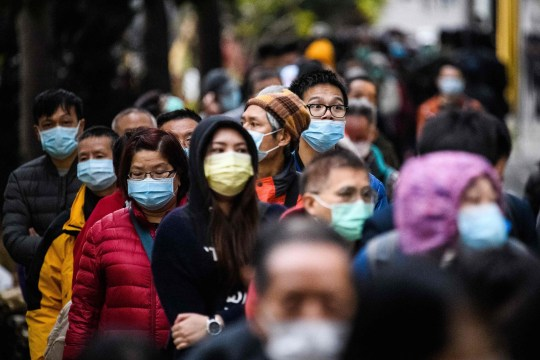 TOPSHOT - People wearing facemasks as a preventative measure following a coronavirus outbreak which began in the Chinese city of Wuhan, line up to purchase face masks from a makeshift stall after queueing for hours following a registration process during which they were given a pre-sales ticket, in Hong Kong on February 5, 2020. - The new coronavirus which appeared late December has claimed nearly 500 lives, infected more than 24,000 people in mainland China and spread to more than 20 countries. (Photo by Anthony WALLACE / AFP) (Photo by ANTHONY WALLACE/AFP via Getty Images)