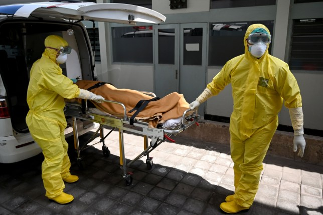 Health workers wearing protective gear take part in an exercise in handling a suspected patient at Sanglah hopital in Denpasar, Indonesia's resort island of Bali, on February 12, 2020. - The number of fatalities from China's COVID-19 coronavirus epidemic jumped to 1,113 nationwide on February 12 after another 97 deaths were reported by the national health commission. (Photo by SONNY TUMBELAKA / AFP) (Photo by SONNY TUMBELAKA/AFP via Getty Images)