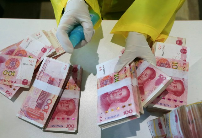 A bank clerk disinfects banknotes in the headquarters of the Suining Bank in Suining city in southwest China's Sichuan province Wednesday, Feb. 26, 2020. China's central bank has ordered banks to ensure the safety of the cash circulation through putting money through quarantine period or disinfection and destroying cash from places like hospital and public transport services to curb the spread of the coronavirus. (Chinatopix Via AP)