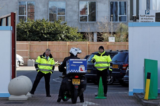 A motorcycle courier arrives at the boarded-off entrance to the Holiday Inn hotel, close to Heathrow Airport, west of London on March 1, 2020. - Britain's Department of Health has block-booked a hotel close to London Heathrow Airport, to use as a quarantine zone for any people entering the country who may have been exposed to the new coronavirus. (Photo by Adrian DENNIS / AFP) (Photo by ADRIAN DENNIS/AFP via Getty Images)