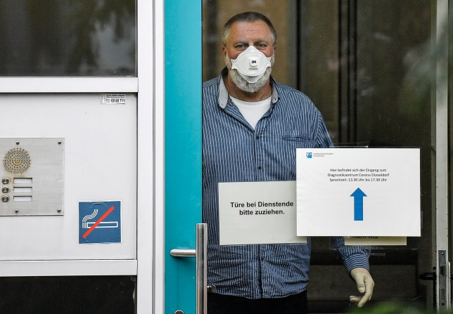 an employee with face mask and gloves waits behind the door of the corona diagnostic center in Duesseldorf, Germany