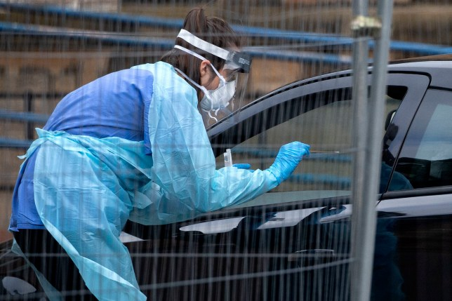 A health worker offers a swab through a car window at a 'drive-through' coronavirus testing facility at the Western General Hospital in Edinburgh. PA Photo. Picture date: Monday March 2, 2020. As many as four in five people in Scotland are expected to become infected by coronavirus at some point, according to chief medical officer Dr Catherine Calderwood, who forecast 4% will need hospital treatment. See PA story HEALTH Coronavirus Scotland. Photo credit should read: Jane Barlow/PA Wire
