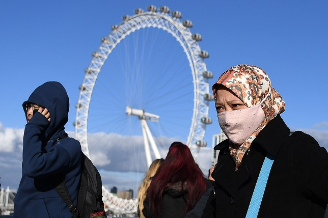 TOPSHOT - A woman wearing a face mask walks across Westminster Bridge, near the London Eye landmark in central London on March 2, 2020. - Britain's Prime Minister Prime Minister on Monday chaired an emergency COBRA meeting on the coronavirus outbreak, as the number of confirmed cases of COVID-19 in the United Kingdom rose to 40. (Photo by DANIEL LEAL-OLIVAS / AFP) (Photo by DANIEL LEAL-OLIVAS/AFP via Getty Images)