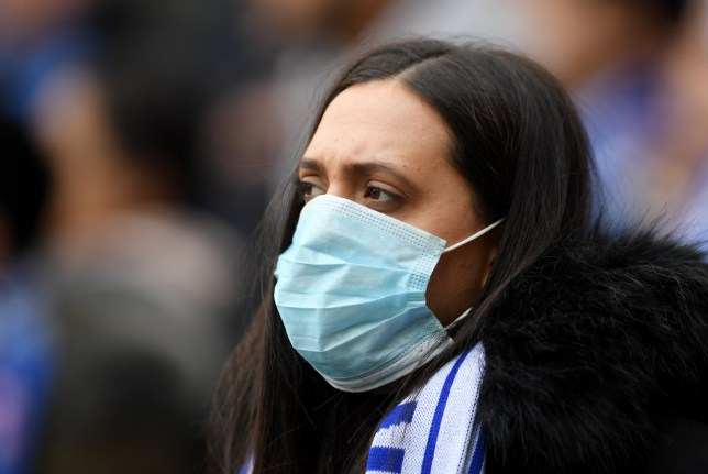 LONDON, ENGLAND - MARCH 08: A fan is seen wearing a disposable face mask prior to the Premier League match between Chelsea FC and Everton FC at Stamford Bridge on March 08, 2020 in London, United Kingdom. (Photo by Mike Hewitt/Getty Images)