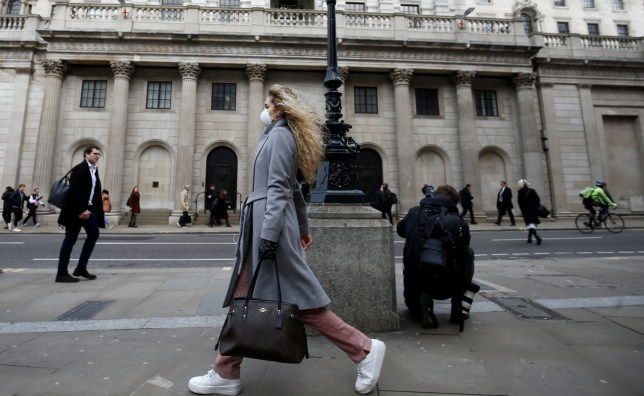 A woman, wearing a protective face mask, walks in front of the Bank of England, following an outbreak of the coronavirus, in London, Britain March 11, 2020. REUTERS/Henry Nicholls