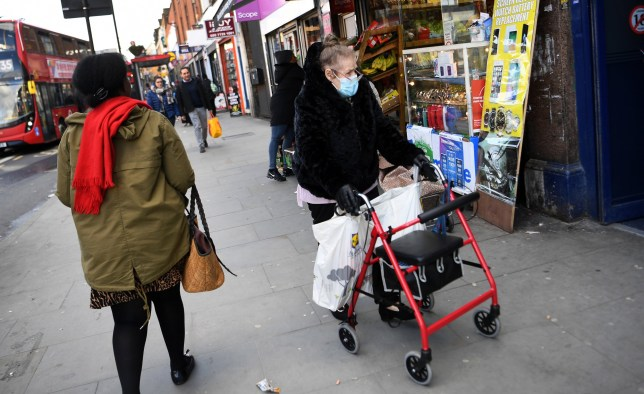 An elderly woman wears a face mask while out shopping in London