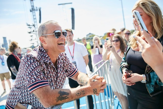 Robbie Williams does a media call prior to his performance at the Grand Prix World Tour event in Melbourne this weekend. Robbie was seen only greeting people by touching elbows, instead of shaking hands, amidst Corona virus contagion fears 12 March 2020 ??MEDIA-MODE.COM