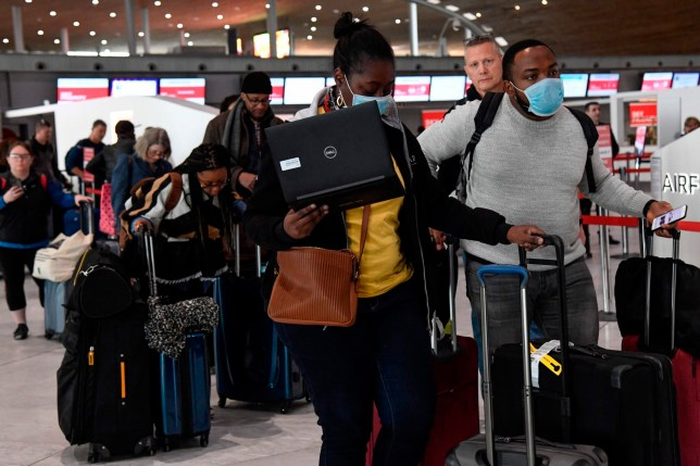 Travellers with protective face mask queue at an airport