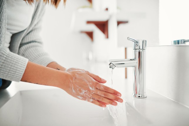 Cropped shot of a woman washing her hands in the bathroom at home